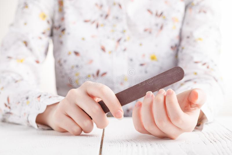 η προσοχή σωμάτων δίνει τα καρφιά που γυαλίζουν τη γυναίκα Γυαλίζοντας νύχια γυναικών με το FI καρφιών στοκ φωτογραφία