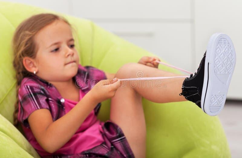 Η προσπάθεια - το χαριτωμένο μικρό κορίτσι δένει το παπούτσι στοκ φωτογραφία