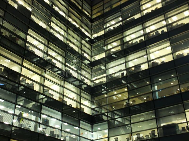 Η πυράκτωση φώτισε τα παράθυρα σε ένα μεγάλο σύγχρονο γεωμετρικό κτίριο γραφείων πόλεων που παρουσιάζει τη νύχτα διαστήματα εργασ στοκ φωτογραφίες