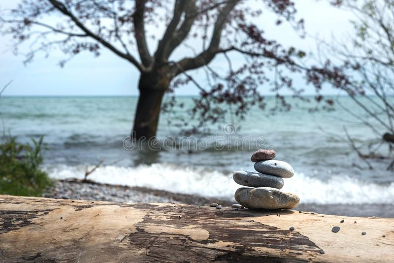 Η πυραμίδα των πετρών με το δέντρο στο νερό ως υπόβαθρο στοκ φωτογραφία