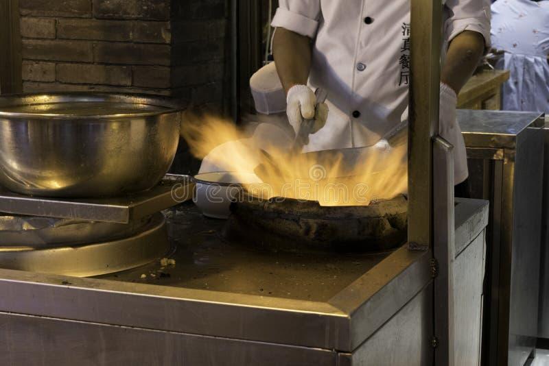 Η πυρκαγιά και τα τρόφιμα ένας κινεζικός αρχιμάγειρας προετοιμάζουν τα τρόφιμα σε ένα wok στοκ φωτογραφία