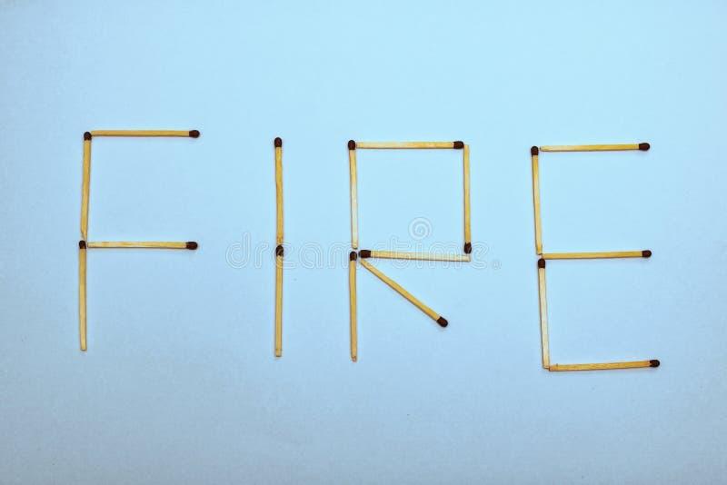 Η πυρκαγιά λέξης σχεδιάζεται από τις αντιστοιχίες σε ένα μπλε υπόβαθρο στοκ εικόνες