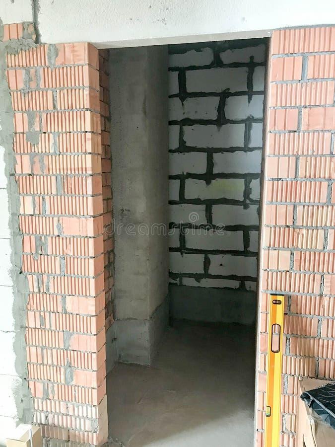 Η πόρτα στο νέο κτήριο με ένα ελεύθερο σχέδιο, σε ένα διαμέρισμα χωρίς επισκευή με τους τοίχους των φραγμών τούβλινων και πυριτικ στοκ φωτογραφία με δικαίωμα ελεύθερης χρήσης