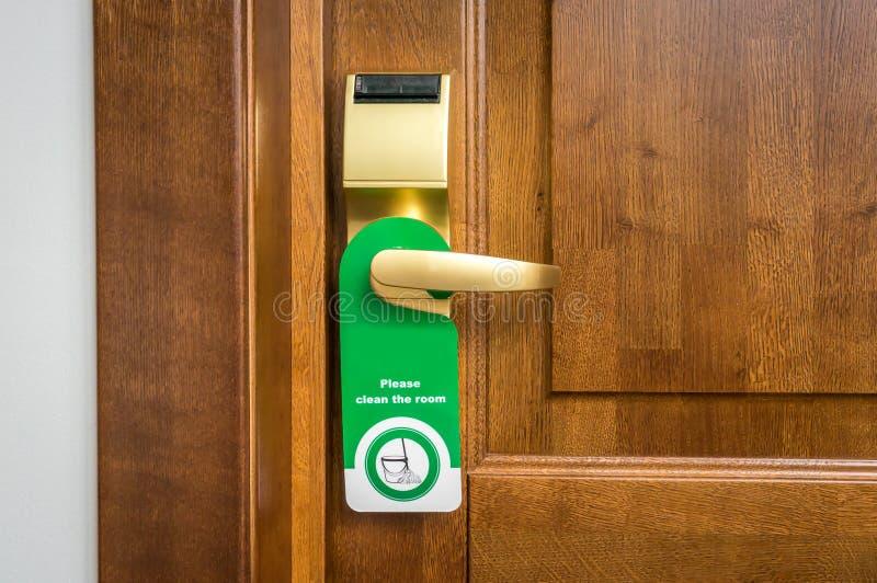 Η πόρτα του δωματίου ξενοδοχείου με το σημάδι παρακαλώ καθαρίζει το δωμάτιο στοκ εικόνες