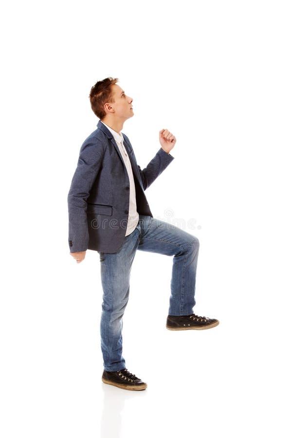 Η πλάγια όψη ενός επιχειρηματία αναρριχείται στα σκαλοπάτια στοκ εικόνα