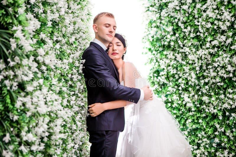 Η πλάγια όψη του ρομαντικού γαμήλιου ζεύγους με τα μάτια έκλεισε το αγκάλιασμα στη μέση των διακοσμήσεων λουλουδιών στοκ φωτογραφία