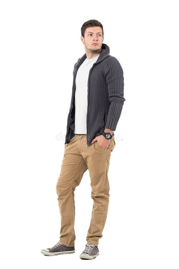 Η πλάγια όψη του όμορφου ατόμου στο γκρίζο ανοιγμένο φερμουάρ πουλόβερ με παραδίδει τις τσέπες ξανακοιτάζοντας πέρα από τον ώμο στοκ φωτογραφίες
