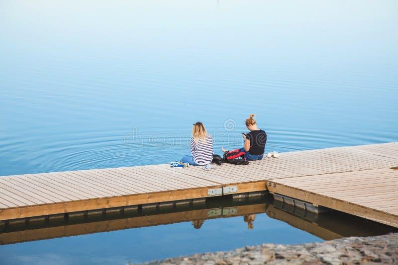 Η Ρωσία, Ροστόφ--φορά στις 3 Ιουνίου 2018 δύο κορίτσια κάθεται στη γέφυρα κοντά στη μεγάλη λίμνη στοκ φωτογραφίες με δικαίωμα ελεύθερης χρήσης