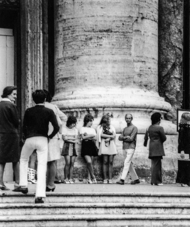Η Ρώμη, Ιταλία, 1970 - τρία κορίτσια στα miniskirts στηρίζεται στο πλήθος στο πόδι μιας στήλης στοκ φωτογραφία