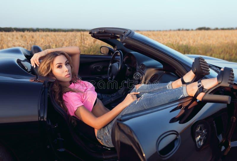 Η σαγηνευτική όμορφη νέα γυναίκα έντυσε στα τζιν και το θέμα που βρίσκονται στο καμπριολέ αυτοκινήτων Υπαίθριο πορτρέτο σε έναν δ στοκ εικόνες