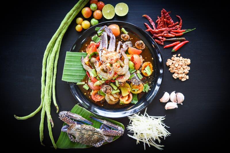 Η σαλάτα θαλασσινών πικάντικη με φρέσκα cockles καβουριών γαρίδων εξυπηρέτησε στα μαύρα χορτάρια φρέσκων λαχανικών πιάτων και τα  στοκ φωτογραφία με δικαίωμα ελεύθερης χρήσης