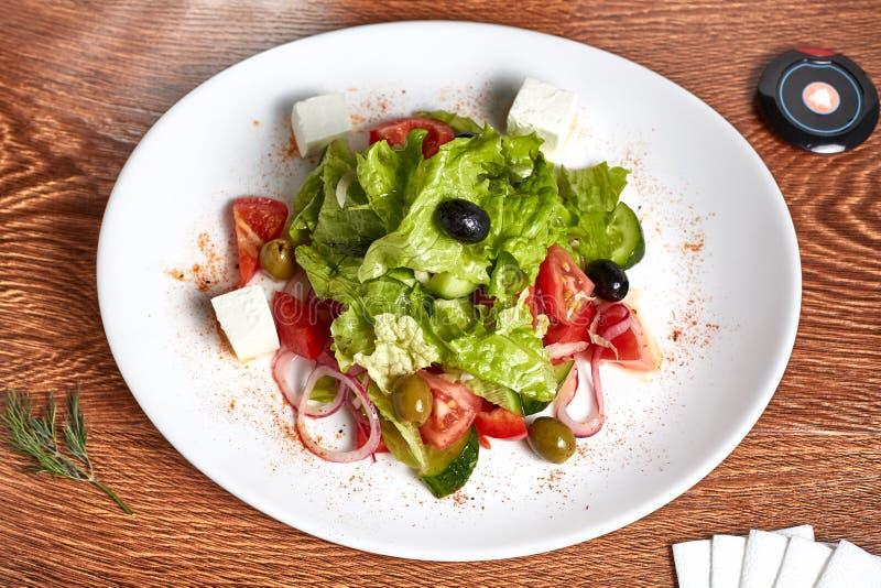 Η σαλάτα με το τυρί μοτσαρελών από τα αγγούρια, ντομάτες, ελιές, πιπέρια κουδουνιών, δαχτυλίδια κρεμμυδιών, μαρούλι, βρίσκεται σε στοκ εικόνα