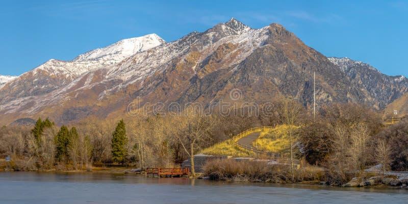 Η σαφής παγωμένη λίμνη πανοράματος και το εντυπωσιακό χιόνι κάλυψαν το βουνό ενάντια στο δονούμενο μπλε ουρανό το χειμώνα στοκ εικόνες με δικαίωμα ελεύθερης χρήσης
