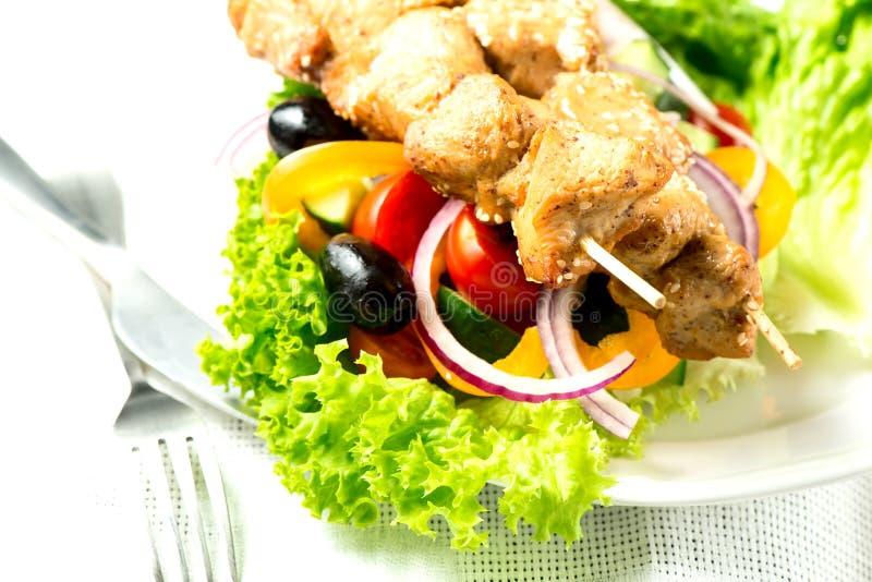 Η σαλάτα με συναντά τα λαχανικά και τα πράσινα στο πιάτο στα WI επιτραπέζιων υφασμάτων στοκ φωτογραφία