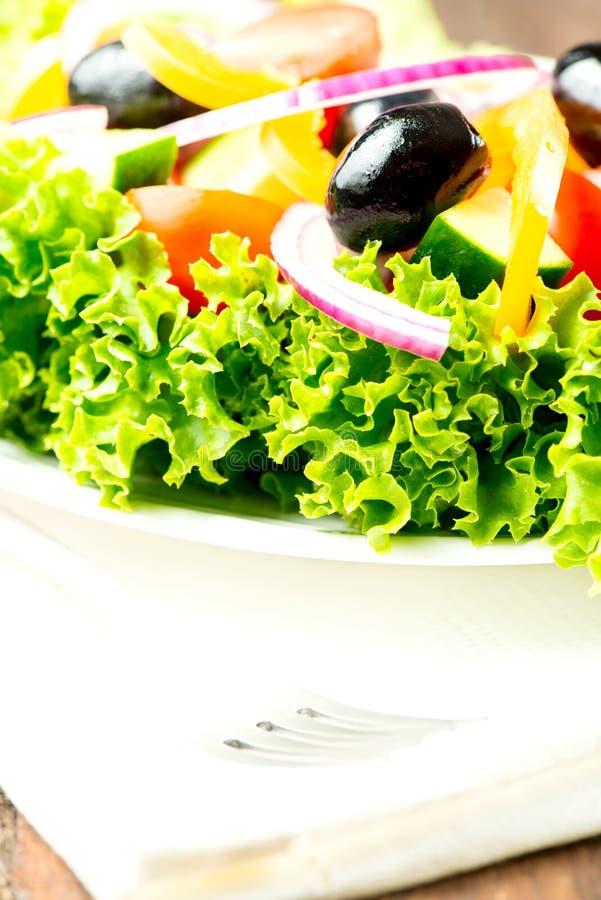 Η σαλάτα με τα λαχανικά και τα πράσινα στο πιάτο στο επιτραπέζιο ύφασμα κλείνουν το u στοκ φωτογραφία