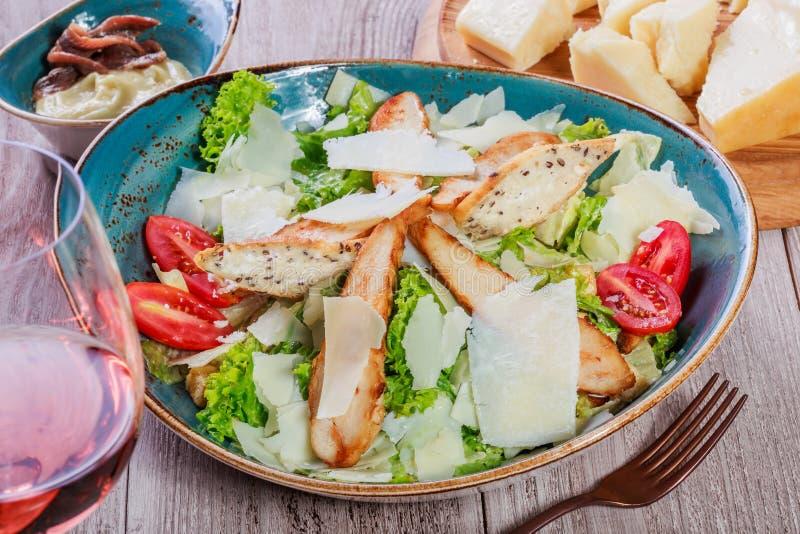 Η σαλάτα με το στήθος κοτόπουλου, τυρί παρμεζάνας, croutons, ντομάτες, ανάμιξε τα πράσινα, το μαρούλι και το ποτήρι του κρασιού στοκ φωτογραφίες