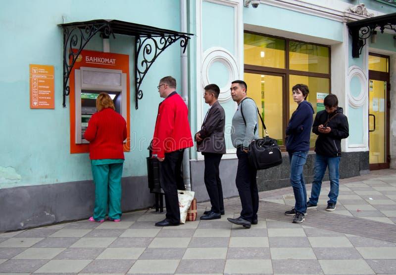 Η σειρά αναμονής των ανθρώπων σε μια οδό ATM στοκ εικόνα