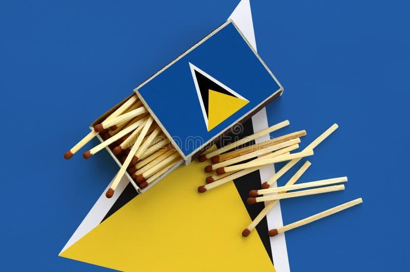 Η σημαία Αγιών Λουκία παρουσιάζεται σε ένα ανοικτό σπιρτόκουτο, από το οποίο διάφορες αντιστοιχίες αφορούν και βρίσκονται μια μεγ στοκ εικόνα