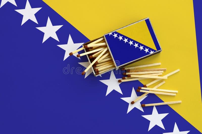 Η σημαία Βοσνίας-Ερζεγοβίνης παρουσιάζεται σε ένα ανοικτό σπιρτόκουτο, από το οποίο διάφορες αντιστοιχίες αφορούν και βρίσκονται  στοκ εικόνα
