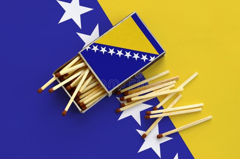Η σημαία Βοσνίας-Ερζεγοβίνης παρουσιάζεται σε ένα ανοικτό σπιρτόκουτο, από το οποίο διάφορες αντιστοιχίες αφορούν και βρίσκονται  στοκ φωτογραφία