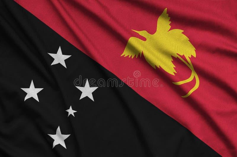 Η σημαία Παπούα Νέα Γουϊνέα απεικονίζεται σε ένα ύφασμα αθλητικών υφασμάτων με πολλές πτυχές Έμβλημα αθλητικών ομάδων στοκ φωτογραφίες