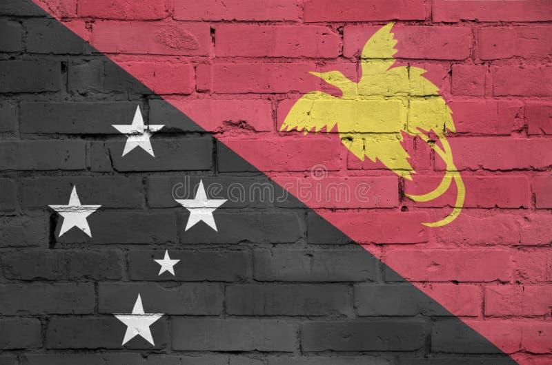 Η σημαία Παπούα Νέα Γουϊνέα είναι χρωματισμένη επάνω σε έναν παλαιό τουβλότοιχο στοκ εικόνες