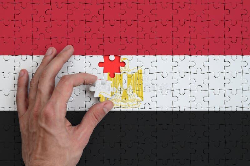 Η σημαία της Αιγύπτου απεικονίζεται σε έναν γρίφο, τον οποίο το χέρι ατόμων ` s ολοκληρώνει για να διπλώσει στοκ εικόνες