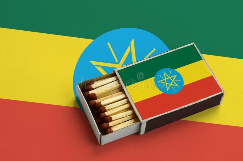 Η σημαία της Αιθιοπίας παρουσιάζεται σε ένα ανοικτό σπιρτόκουτο, το οποίο γεμίζουν με τις αντιστοιχίες και βρίσκεται σε μια μεγάλ στοκ φωτογραφία με δικαίωμα ελεύθερης χρήσης