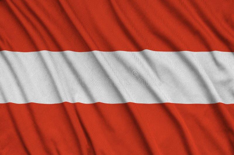 Η σημαία της Αυστρίας απεικονίζεται σε ένα ύφασμα αθλητικών υφασμάτων με πολλές πτυχές Έμβλημα αθλητικών ομάδων στοκ εικόνα