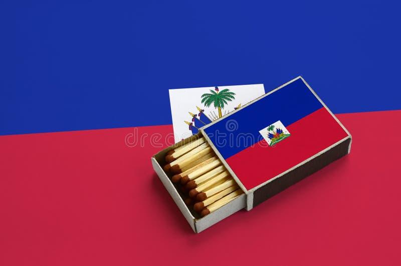 Η σημαία της Αϊτής παρουσιάζεται σε ένα ανοικτό σπιρτόκουτο, το οποίο γεμίζουν με τις αντιστοιχίες και βρίσκεται σε μια μεγάλη ση στοκ εικόνες
