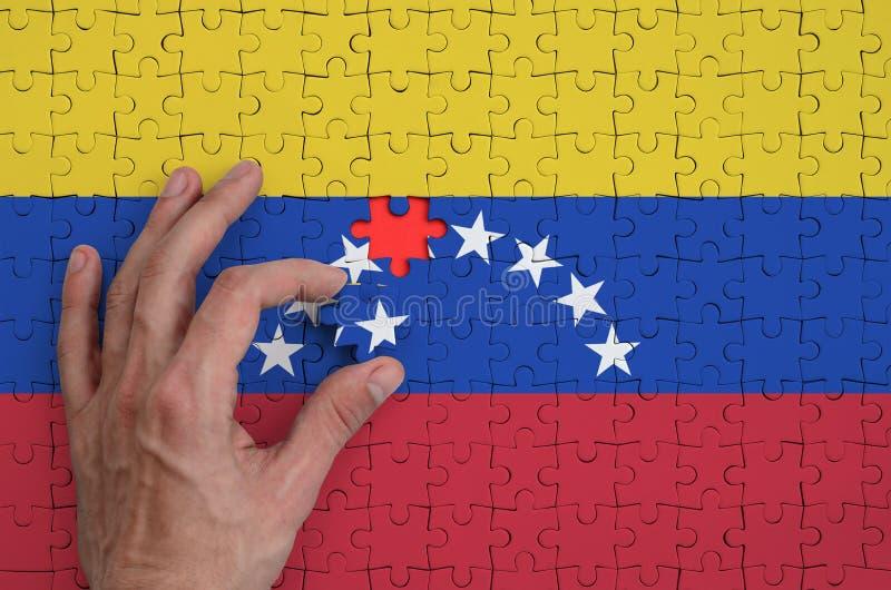 Η σημαία της Βενεζουέλας απεικονίζεται σε έναν γρίφο, τον οποίο το χέρι ατόμων ` s ολοκληρώνει για να διπλώσει στοκ φωτογραφίες