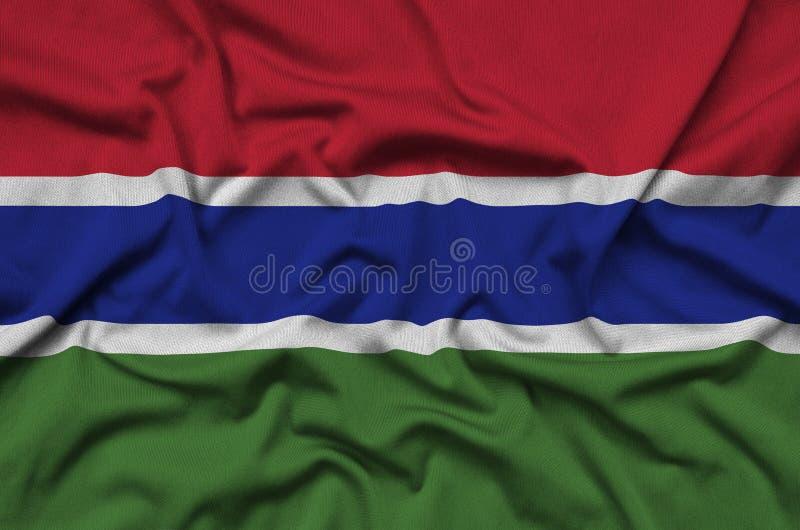 Η σημαία της Γκάμπιας απεικονίζεται σε ένα ύφασμα αθλητικών υφασμάτων με πολλές πτυχές Έμβλημα αθλητικών ομάδων στοκ εικόνες
