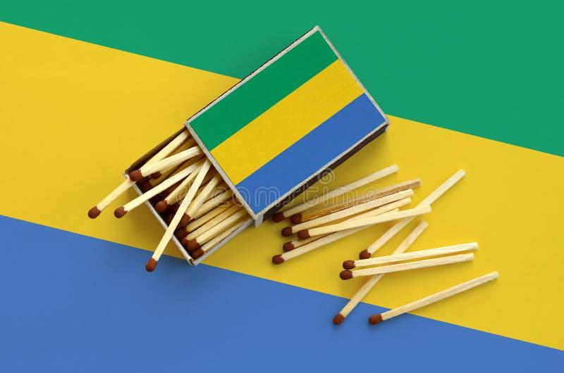 Η σημαία της Γκαμπόν παρουσιάζεται σε ένα ανοικτό σπιρτόκουτο, από το οποίο διάφορες αντιστοιχίες αφορούν και βρίσκονται μια μεγά στοκ εικόνα με δικαίωμα ελεύθερης χρήσης
