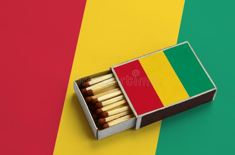 Η σημαία της Γουινέας παρουσιάζεται σε ένα ανοικτό σπιρτόκουτο, το οποίο γεμίζουν με τις αντιστοιχίες και βρίσκεται σε μια μεγάλη στοκ φωτογραφία με δικαίωμα ελεύθερης χρήσης
