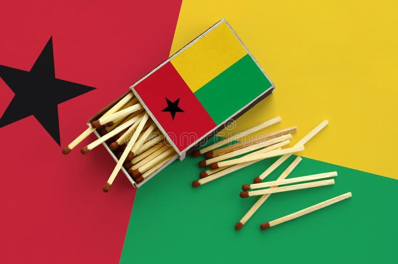 Η σημαία της Γουινέα-Μπισσάου παρουσιάζεται σε ένα ανοικτό σπιρτόκουτο, από το οποίο διάφορες αντιστοιχίες αφορούν και βρίσκονται στοκ φωτογραφία
