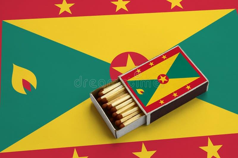 Η σημαία της Γρενάδας παρουσιάζεται σε ένα ανοικτό σπιρτόκουτο, το οποίο γεμίζουν με τις αντιστοιχίες και βρίσκεται σε μια μεγάλη στοκ φωτογραφίες με δικαίωμα ελεύθερης χρήσης
