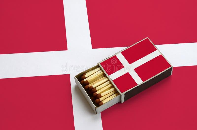 Η σημαία της Δανίας παρουσιάζεται σε ένα ανοικτό σπιρτόκουτο, το οποίο γεμίζουν με τις αντιστοιχίες και βρίσκεται σε μια μεγάλη σ στοκ φωτογραφία με δικαίωμα ελεύθερης χρήσης