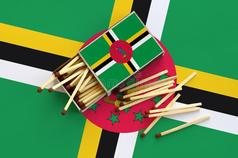 Η σημαία της Δομίνικας παρουσιάζεται σε ένα ανοικτό σπιρτόκουτο, από το οποίο διάφορες αντιστοιχίες αφορούν και βρίσκονται μια με στοκ φωτογραφίες με δικαίωμα ελεύθερης χρήσης