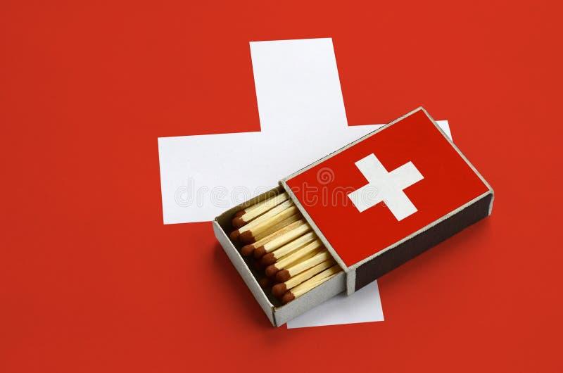 Η σημαία της Ελβετίας παρουσιάζεται σε ένα ανοικτό σπιρτόκουτο, το οποίο γεμίζουν με τις αντιστοιχίες και βρίσκεται σε μια μεγάλη στοκ φωτογραφίες