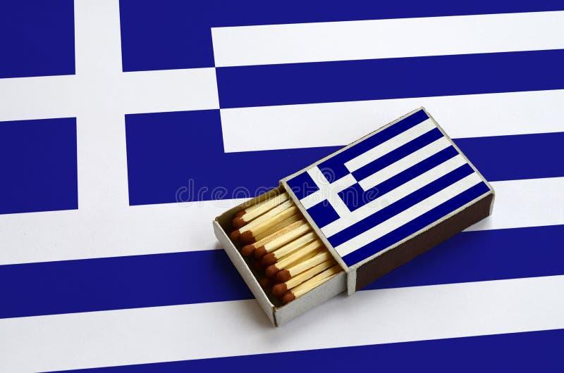 Η σημαία της Ελλάδας παρουσιάζεται σε ένα ανοικτό σπιρτόκουτο, το οποίο γεμίζουν με τις αντιστοιχίες και βρίσκεται σε μια μεγάλη  στοκ εικόνα