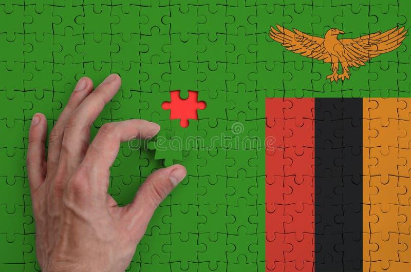 Η σημαία της Ζάμπια απεικονίζεται σε έναν γρίφο, τον οποίο το χέρι ατόμων ` s ολοκληρώνει για να διπλώσει στοκ εικόνες