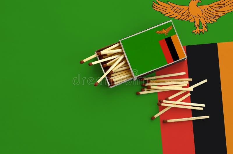 Η σημαία της Ζάμπια παρουσιάζεται σε ένα ανοικτό σπιρτόκουτο, από το οποίο διάφορες αντιστοιχίες αφορούν και βρίσκονται μια μεγάλ στοκ φωτογραφία με δικαίωμα ελεύθερης χρήσης