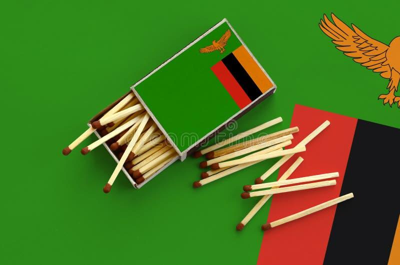Η σημαία της Ζάμπια παρουσιάζεται σε ένα ανοικτό σπιρτόκουτο, από το οποίο διάφορες αντιστοιχίες αφορούν και βρίσκονται μια μεγάλ στοκ εικόνα
