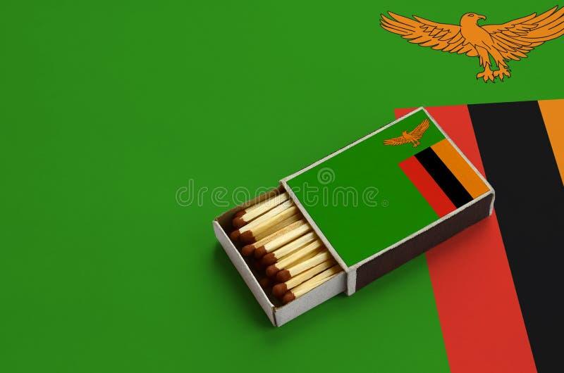Η σημαία της Ζάμπια παρουσιάζεται σε ένα ανοικτό σπιρτόκουτο, το οποίο γεμίζουν με τις αντιστοιχίες και βρίσκεται σε μια μεγάλη σ στοκ εικόνα