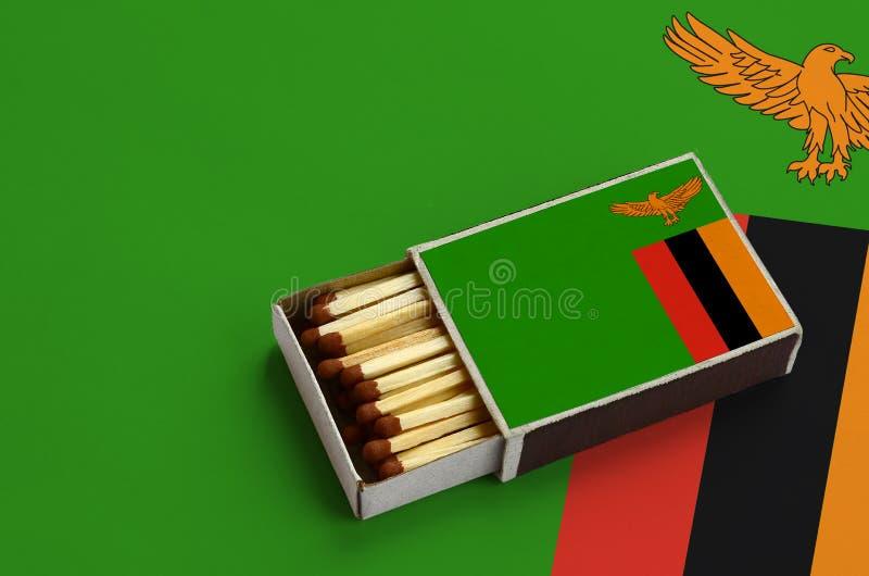 Η σημαία της Ζάμπια παρουσιάζεται σε ένα ανοικτό σπιρτόκουτο, το οποίο γεμίζουν με τις αντιστοιχίες και βρίσκεται σε μια μεγάλη σ στοκ φωτογραφία με δικαίωμα ελεύθερης χρήσης