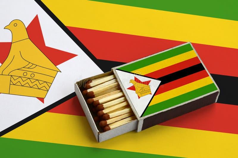 Η σημαία της Ζιμπάμπουε παρουσιάζεται σε ένα ανοικτό σπιρτόκουτο, το οποίο γεμίζουν με τις αντιστοιχίες και βρίσκεται σε μια μεγά στοκ εικόνες
