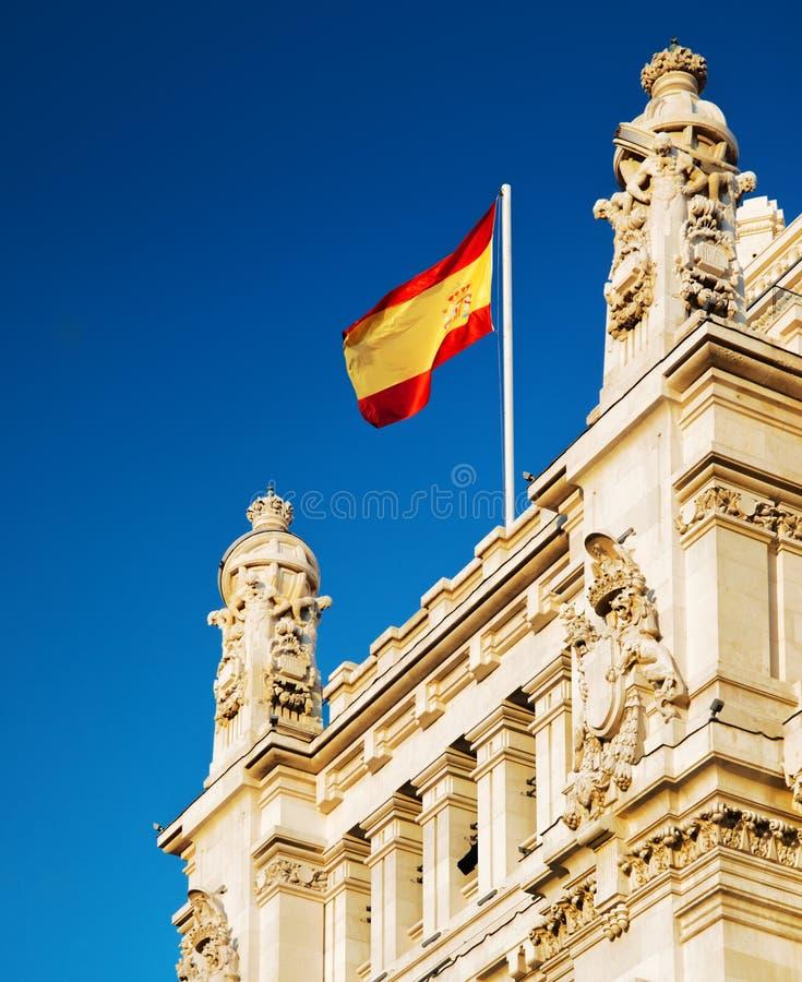 Η σημαία της Ισπανίας που κυματίζει στο παλάτι Cybele στη Μαδρίτη στοκ φωτογραφία