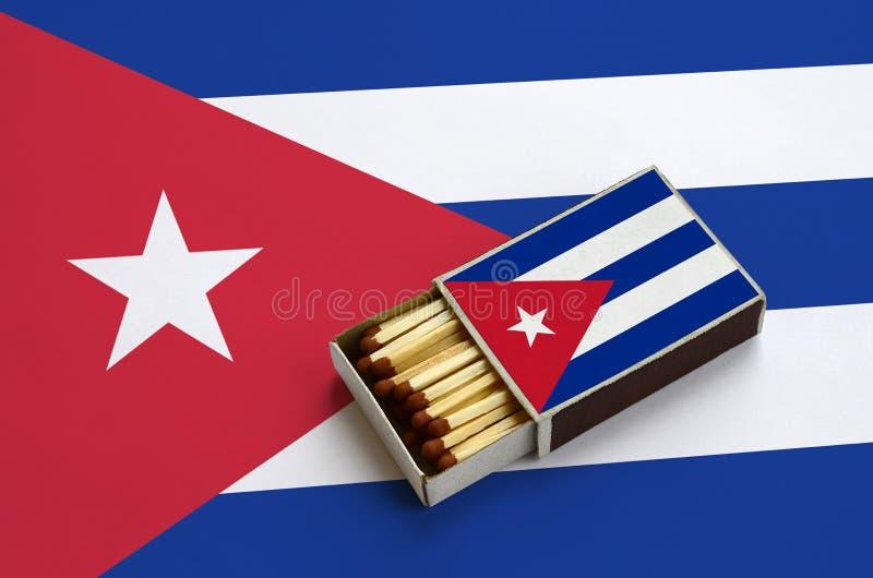 Η σημαία της Κούβας παρουσιάζεται σε ένα ανοικτό σπιρτόκουτο, το οποίο γεμίζουν με τις αντιστοιχίες και βρίσκεται σε μια μεγάλη σ στοκ εικόνα με δικαίωμα ελεύθερης χρήσης