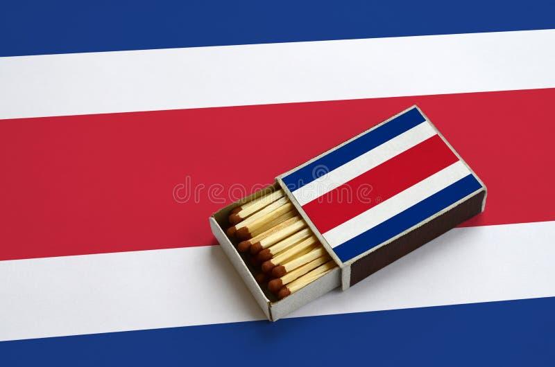 Η σημαία της Κόστα Ρίκα παρουσιάζεται σε ένα ανοικτό σπιρτόκουτο, το οποίο γεμίζουν με τις αντιστοιχίες και βρίσκεται σε μια μεγά στοκ φωτογραφία