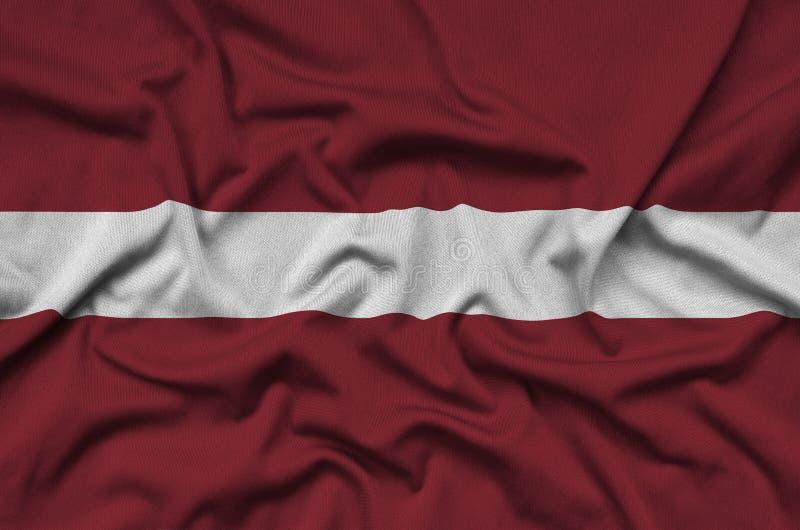 Η σημαία της Λετονίας απεικονίζεται σε ένα ύφασμα αθλητικών υφασμάτων με πολλές πτυχές Έμβλημα αθλητικών ομάδων στοκ φωτογραφία